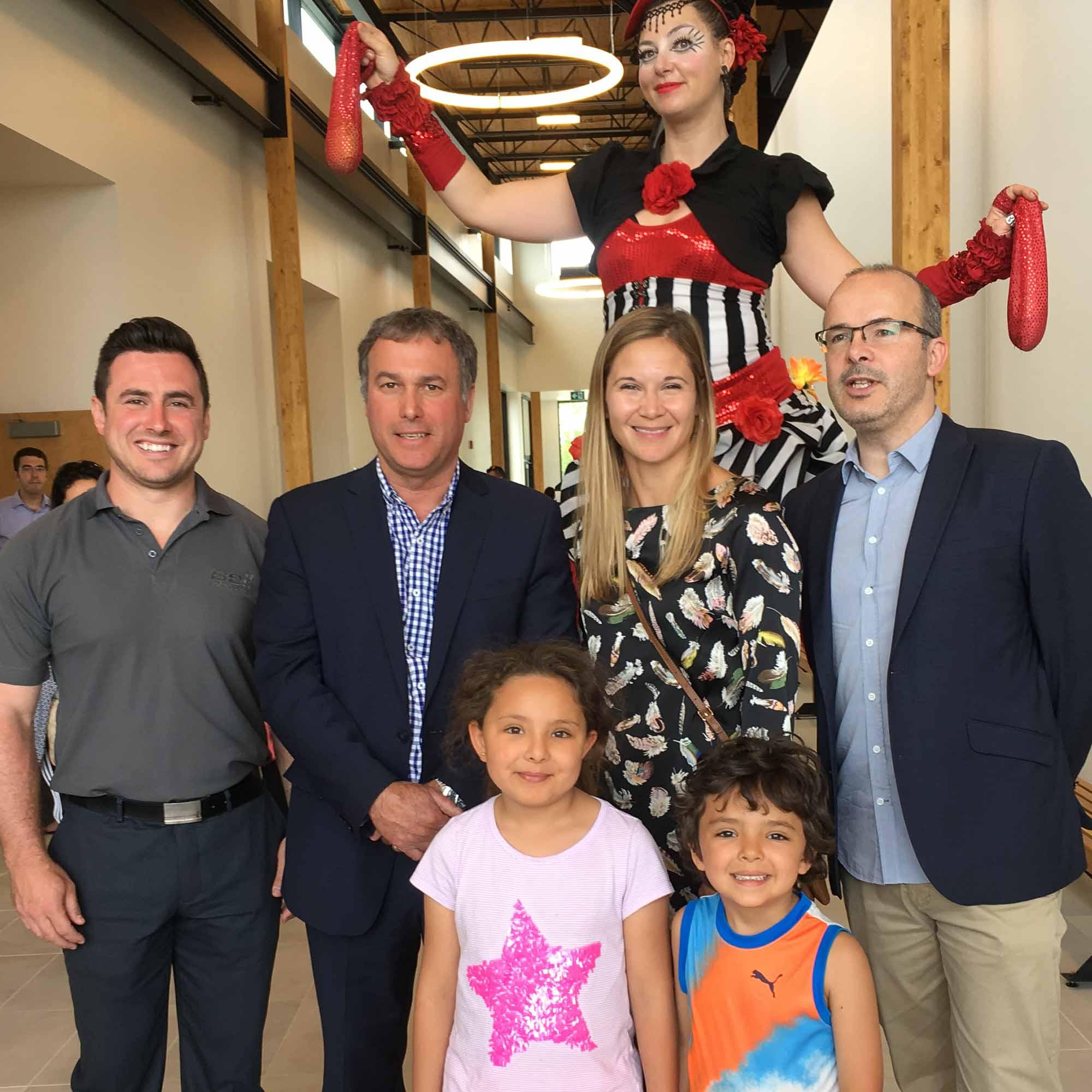 Dans le grand hall, Michael Nault de Bell Helicopter Textron, Jean Bouchard, maire de Mirabel, Isabelle Nuckle d'Hydro-Québec et Martin Brière, architecte et concepteur pour la firme BGLA, posent fièrement avec lesenfants et une dame aux échasses.