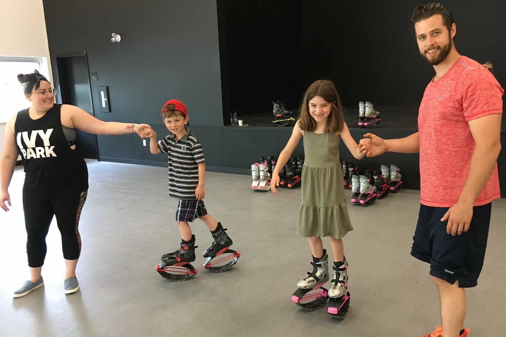 Jessica Desrosiers offrent une initiation de bottes trampolines (kangoo jumps) aux jeunes Tristan et Jade Ducharme dans une des salles disponibles pour des cours ou des ateliers.