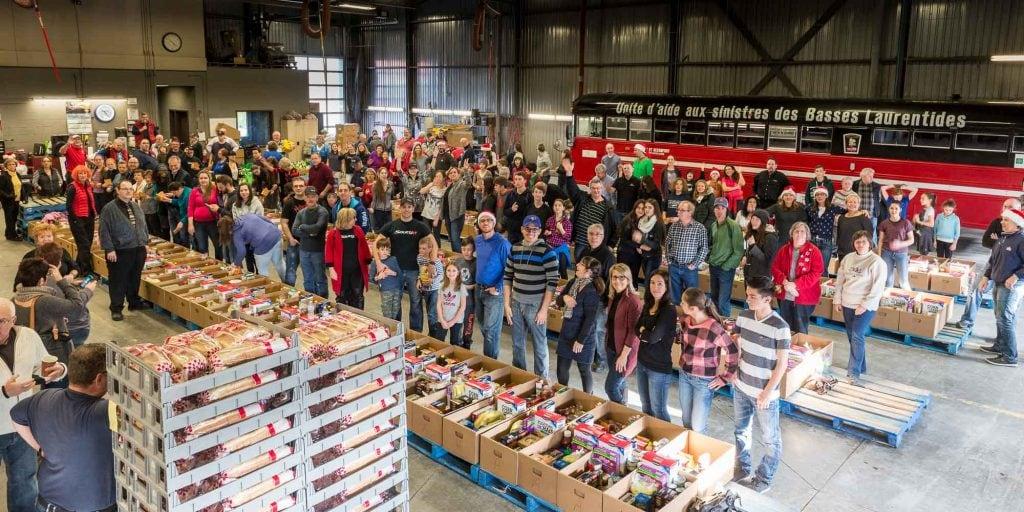 Plus de 250 bénévoles participent à la grande cueillette de paniers de Noël du Club Optimiste de Saint-Jérôme. Ici, dans l'entrepôt d'Inter-Nord, on répartit les aliments dans des boîtes.