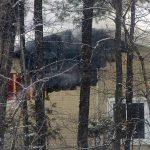 À travers bois, on devine des flammes dans la structure de la maison du chemin Pierre-Péladeau, à Sainte-Adèle, le 28 janvier 2016. Photo Alexandre Parent Léveillé