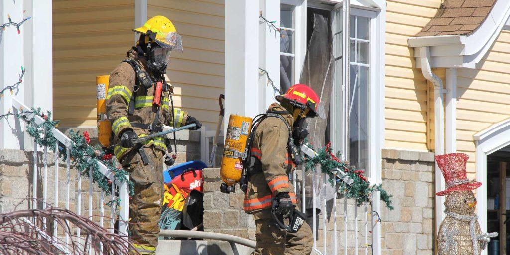 Deux pompiers sortent d'une maison de Prévost, sur la rue Bourque, le 29 mars 2016. Photos par Alexandre Parent Léveillé