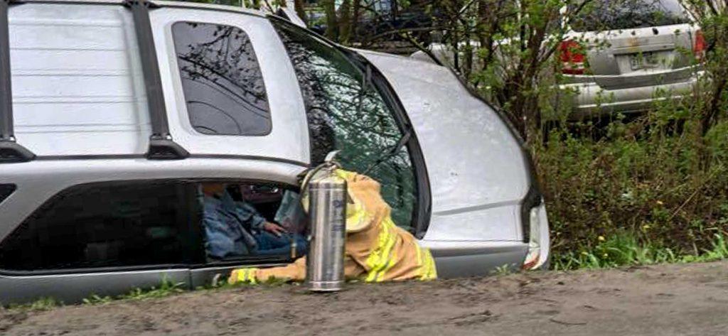 Un pompier et un extincteur sont à côté d'un véhicule qui est arrêté dans le fossé de la montée Masson à Sainte-Sophie, le vendredi 13 mai 2016.