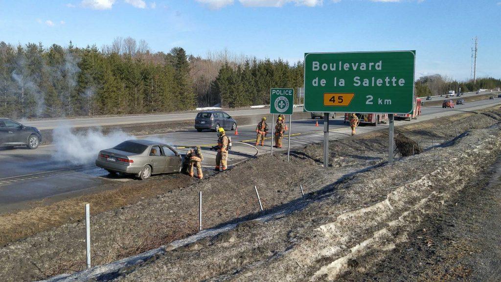 Une voiture en feu est prise en charge par les pompiers de Saint-Jérôme au kilomètre 47 de l'autoroute 15 Sud, le 8 mars 2017.