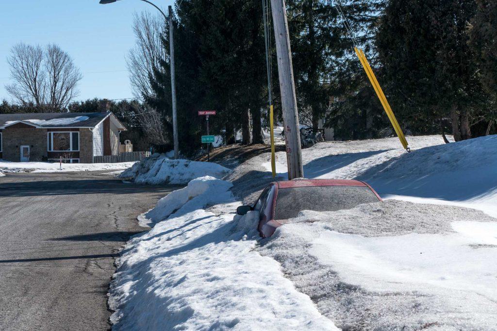 Voiture rouge qui a passé l'hiver sous la neige, sur la rue Jeanneau, à Lafontaine le 22 mars 2017.