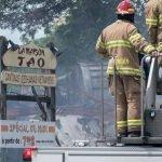 Des pompiers de Saint-Colomban arrosent les débris d'un édifice en démolition sur la rue Labelle, au centre-ville de Saint-Jérôme le 27 juin 2017.