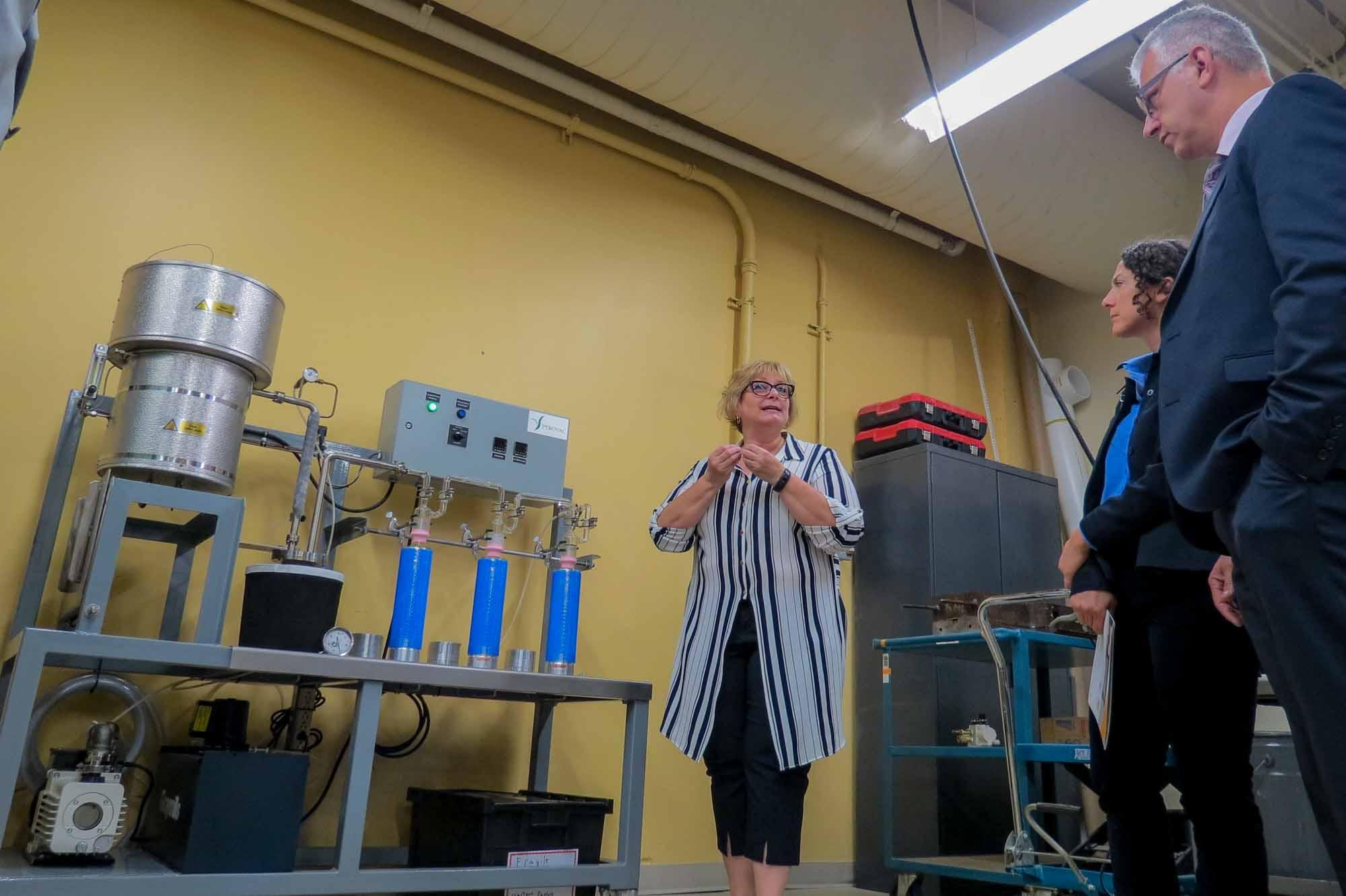 Janic Lauzon, directrice du CDCQ, explique l'utilisation d'un des nouveaux appareils, un réacteur à pyrolyse. À droite, on reconnaît le député d'Argenteuil-La Petite Nation, Stéphane Lauzon.