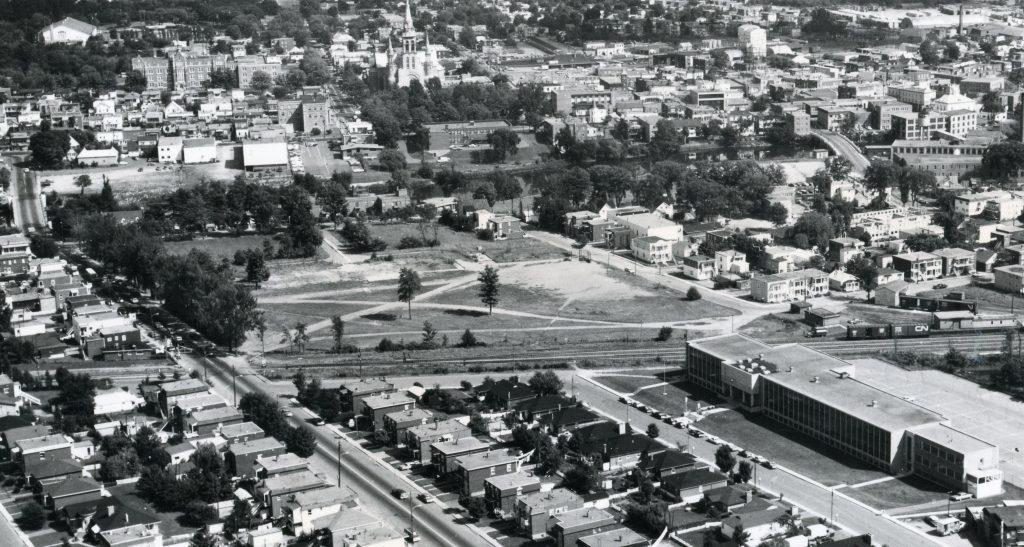 Image aérienne de l'école Mgr-Frenette et du terrain vacant après l'incendie du vieux collège, là où se trouvent aujourd'hui le palais de justice et l'édifice Athanase-David à Saint-Jérôme.