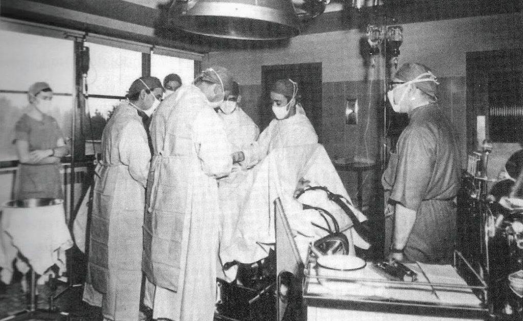 Dans une salle d'opération de l'Hôtel-Dieu de Saint-Jérôme en 1956, le chirurgien Jean-Paul Thibault, de dos au centre, est entouré des docteurs Calixto Requena et Carlos De Torregrossa, de l'anesthésiste Paul Marcoux, ainsi que des gardes Lanthier et Smith. (Photo tirée de l'album souvenir L'Hôtel Dieu de Saint-Jérôme et ses fantômes)