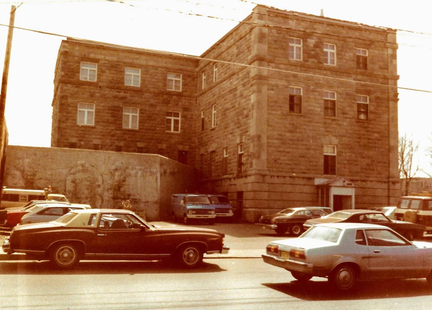 Un épais mur de béton à l'arrière du palais, vu de la rue Labelle.