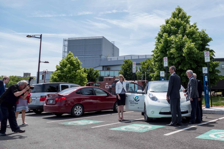 Le maire de Saint-Jérôme Stéphane Maher et les conseillers municipaux Gilles Robert et Bernard Bougie posent devant huit nouvelles bornes électriques installées au stationnement P9 de Saint-Jérôme, le 15 juin 2017.