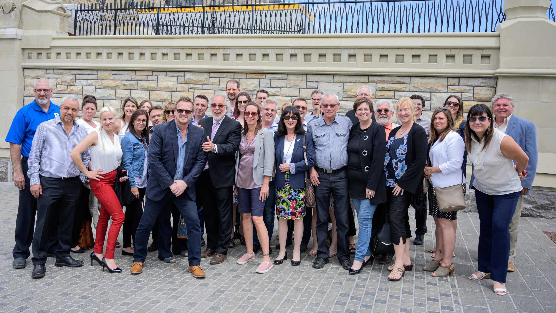 Un joyeux groupe de membres de la Chambre de commerce et d'industrie pose à l'entrée du Parlement d'Ottawa. La Chambre des Communes siège présentement dans un édifice temporaire pendant que la «vraie» chambre, qui se trouve directement derrière la tour de l'édifice, subit des rénovations prévues pour quelques années.