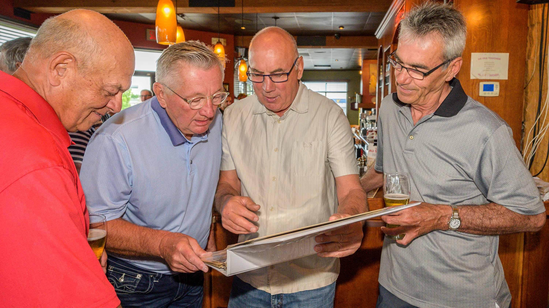Marcel Labelle, Mario Desjardins, Charlie Labelle et Marc Tessier feuilletaient ensemble un album de photos.