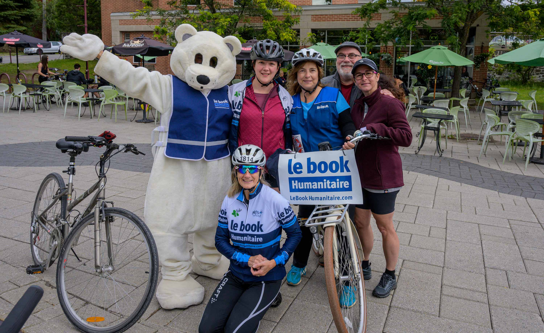 La mascotte du Book humanitaire Bookou, l'initiatrice  de l'événement Catherine Nantel Blais , Coreen Carrière , Mario Martin de Rona Saint-Sauveur, Annie Ashton, et à l'avant, Rachel Lapierre.