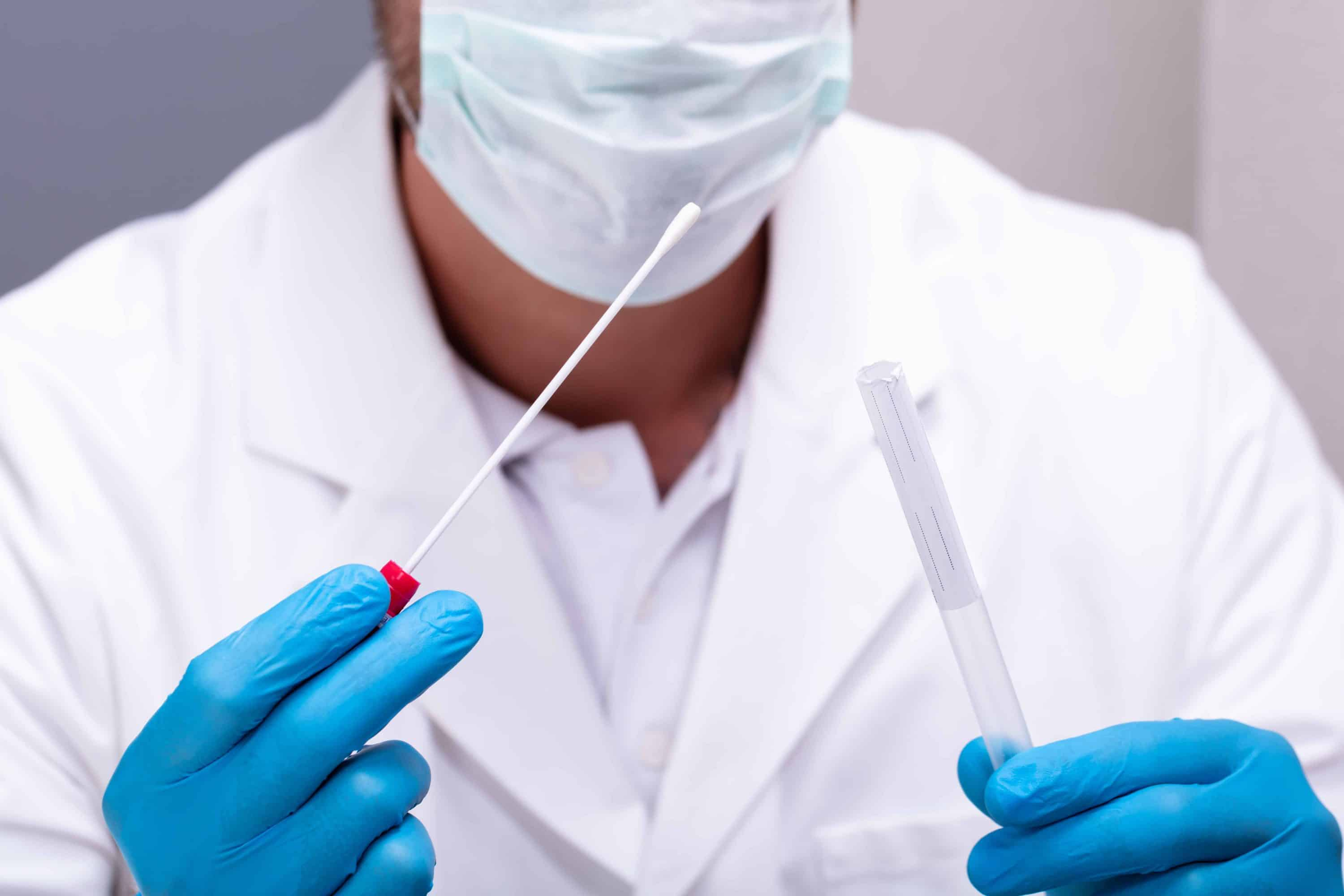Male Doctor Wearing Blue Gloves Holding Cotton Swab And DNA Test Tube